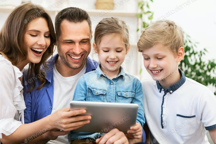 Joyful Family Using Digital Tablet Laughing Watching Movie At Home
