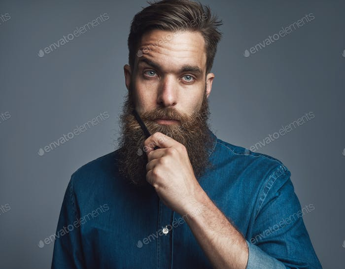 Young man holding his beard with blank stare