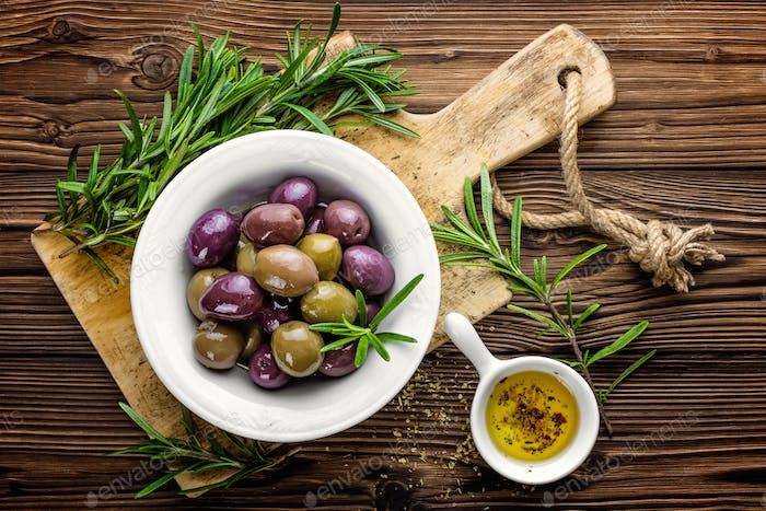 Olives in bowl with olive oil on dark wooden rustic background, above view; italian cuisine