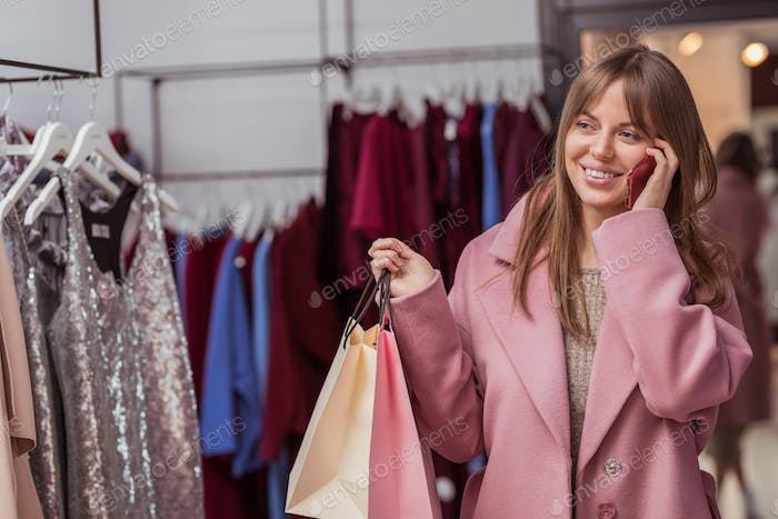Smiling girl with shopping bags in the shop