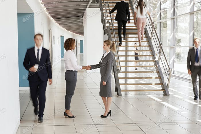 Businesswomen shaking hands in a busy modern lobby