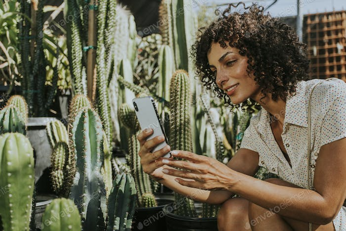 Woman taking photos of cacti at a botanical garden