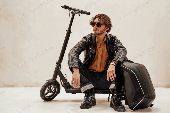 Assertive and rich young man posing on a scooter in a bright studio, looking cool
