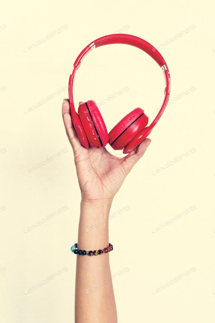 Hand holding headphone isolated on background