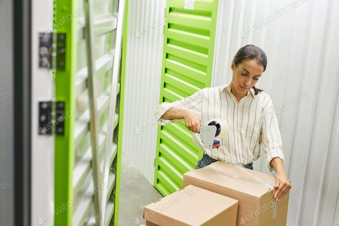 Woman Packing Boxes in Storage Facility