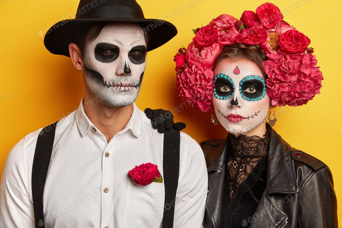 Studio shot of serious couple wears vivid makeup, celebrate traditional mexican holiday, wear wreath
