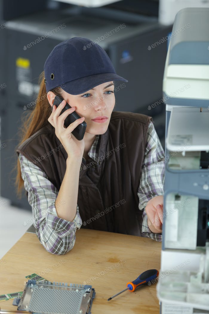 Technician repairing photocopier and talking on cellphone