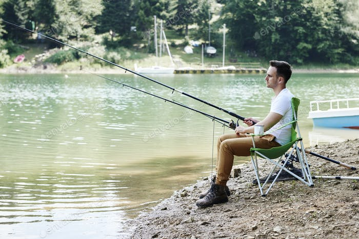 Men with fishing rod sitting on fishing chair