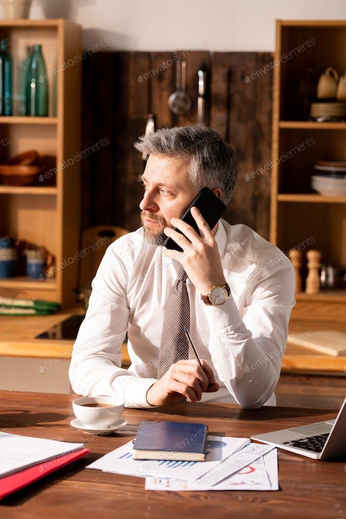 Hombre ocupado hablando por teléfono en la Cocina