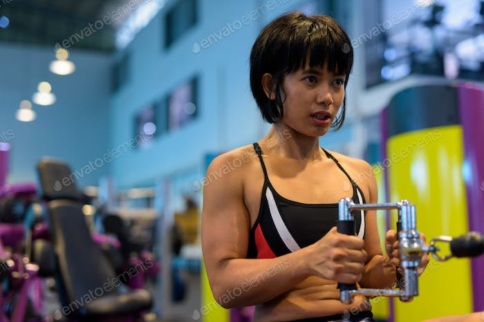 Young woman working back with seated cable row