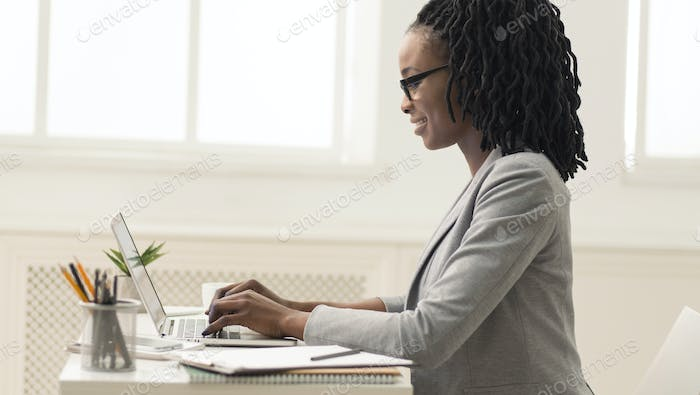 African American Lady Using Laptop In Office, Side View, Panorama