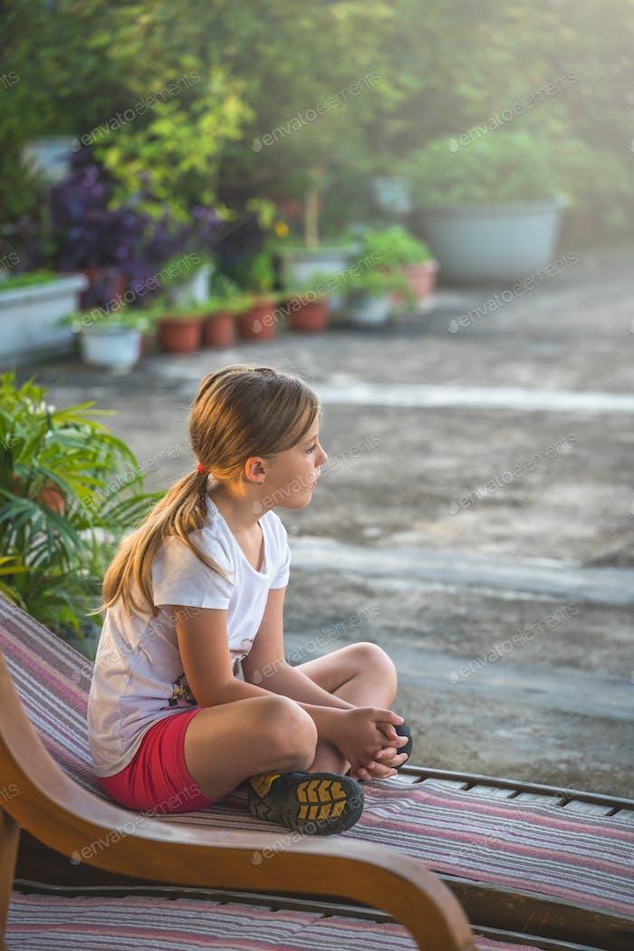 Nettes kaukasisches Mädchen ruht auf einem liegenden Holzstuhl