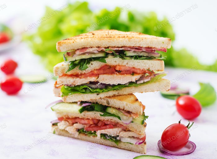 lub sandwich with chicken breast, bacon, tomato, cucumber and herbs