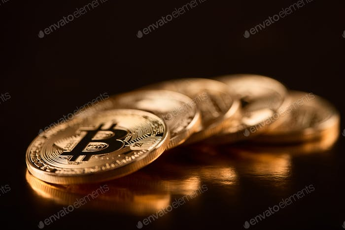 Row of shiny golden bitcoins as main digital currency nowadays isolated on black background