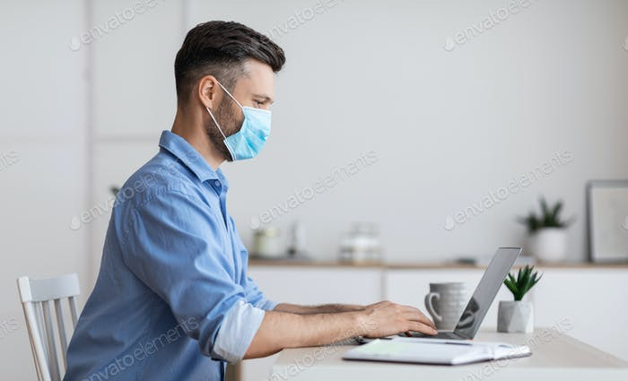 Arbeit während der Pandemie. Geschäftsmann Tragen schützende Gesichtsmaske während der Arbeit an Laptop