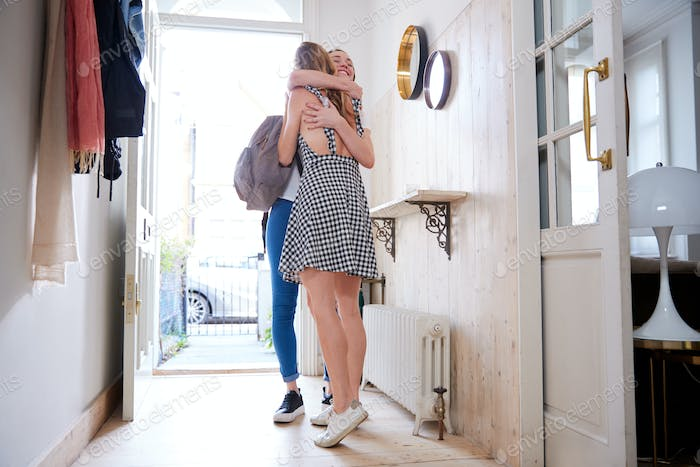 Woman Opening Front Door And Greeting Gay Partner As She Comes Home From Work