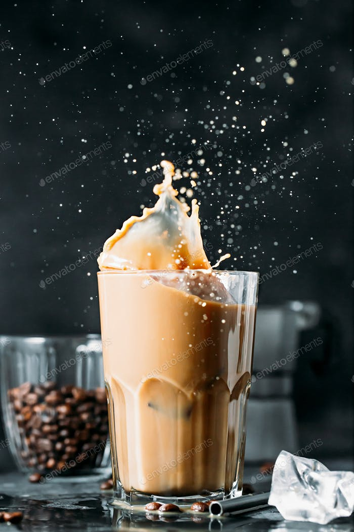 Splash of iced coffee in tall glass and coffee beans.