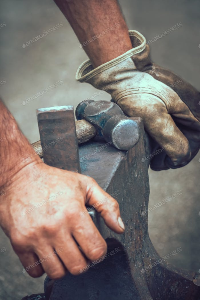 A blacksmith resting his hands on anvil