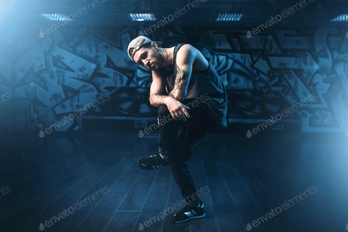 Young male hip hop dancer posing in dance studio