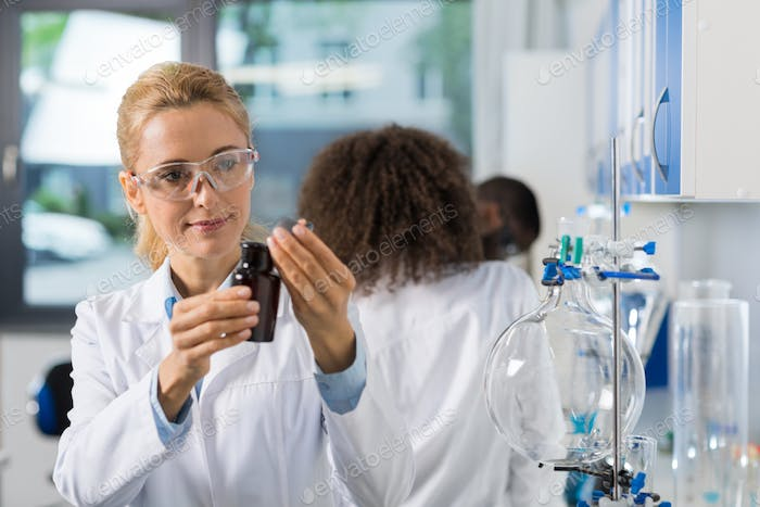 Female Scientific Researcher In Laboratory Doing Research, Woman Working With Chemicals Over Group