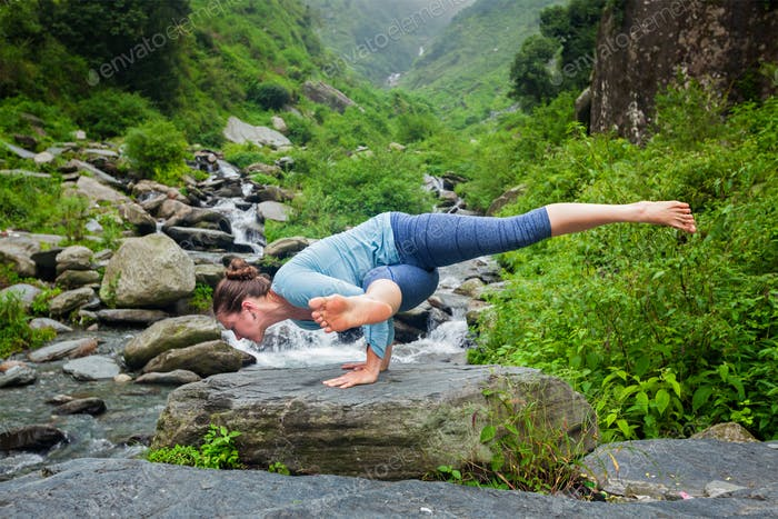 Woman doing yoga oudoors at tropical waterfall