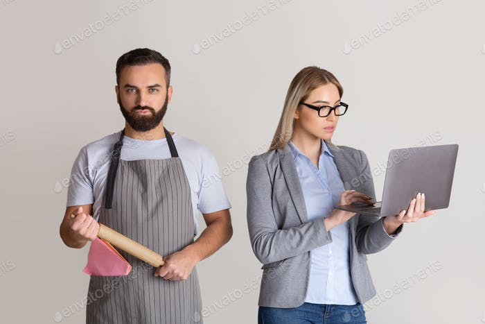Wife in formal suit with glasses and with laptop in hands, man in apron and with rolling pin