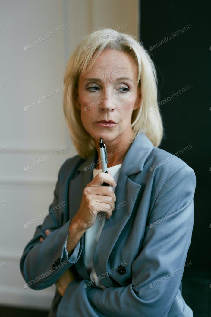 Pensive Senior Businesswoman by Window