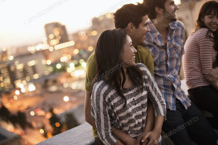 A small group of friends gathered on a rooftop terrace overlooking a city at twilight.