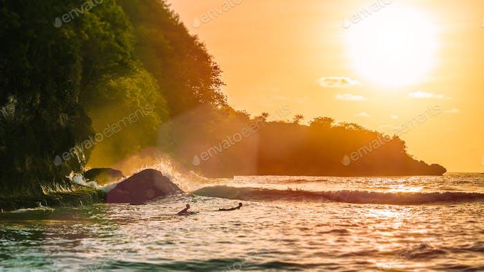 Surfen Sie am Sonnenuntergang auf der wunderschönen Crystal Bay, Nusa Penida, Bali, Indonesien