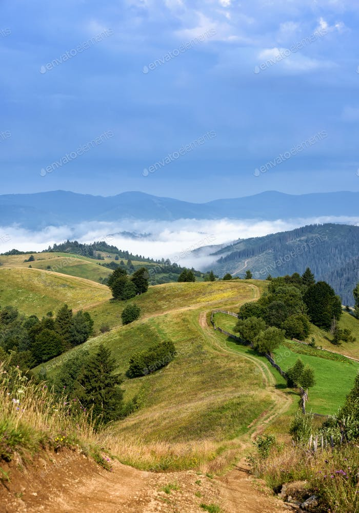 Beautiful rural mountain landscape with road and fog in the vall