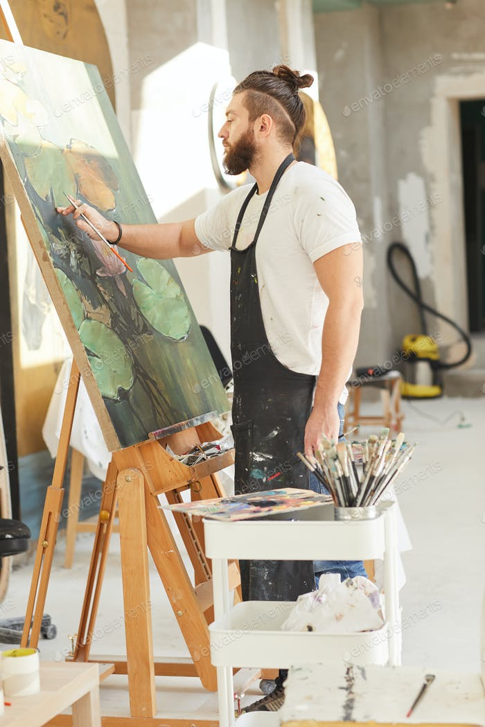 Bearded Male Artist Painting on Easel in Workshop