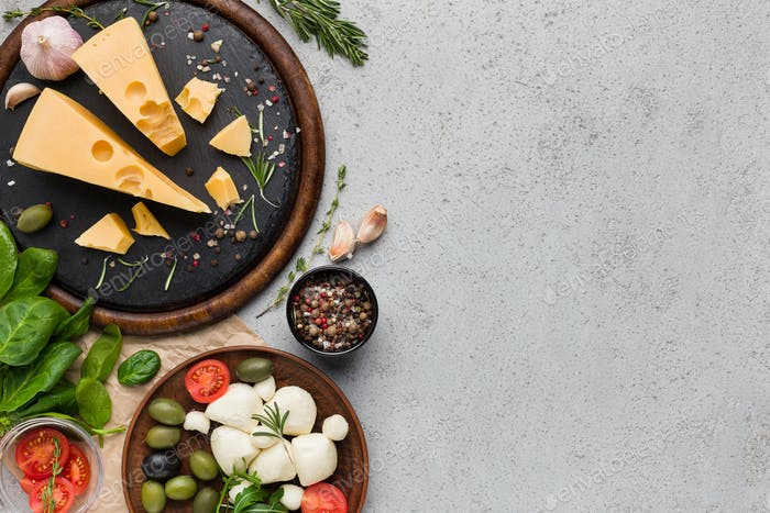 Cheese variety, olives and fresh herbs on concrete background