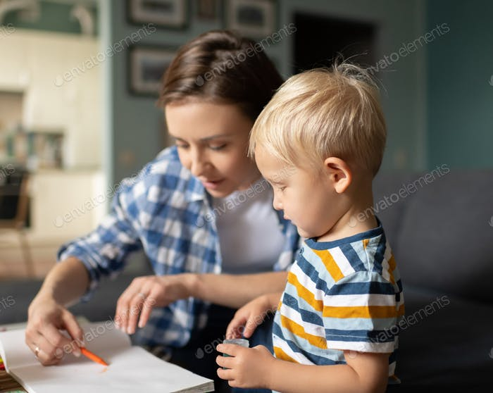 Mother spending time with little son and painting at home