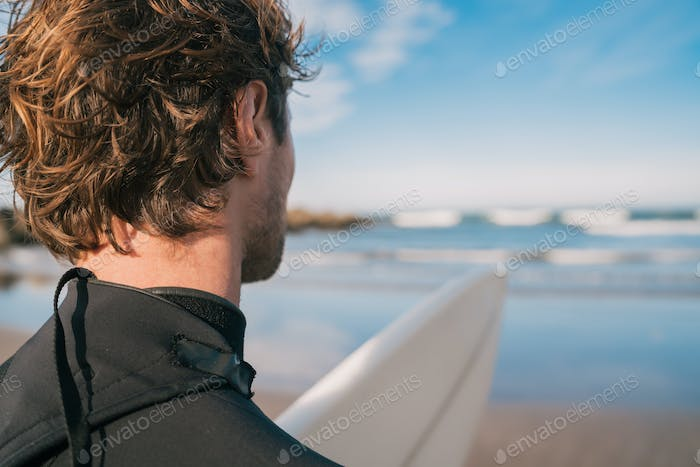 Surfer standing at sandy beach and looking at the sea.