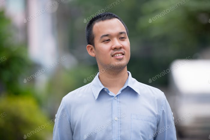 Portrait of happy Asian businessman thinking outdoors