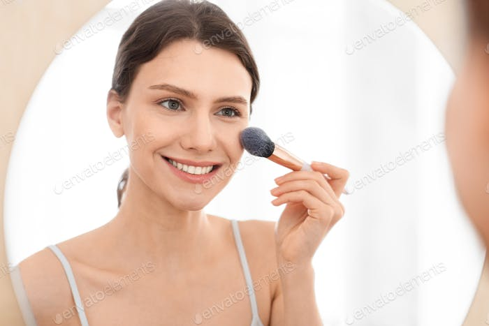 Closeup of attractive woman applying blush on her face