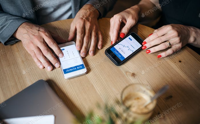 Midsection of businesspeople having business meeting in a cafe, using smartphones.