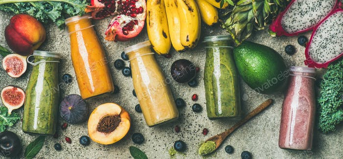 Colorful smoothies in bottles with fresh fruit, copy space