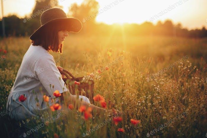 Stylish girl in linen dress gathering flowers sitting in poppy meadow in sunset