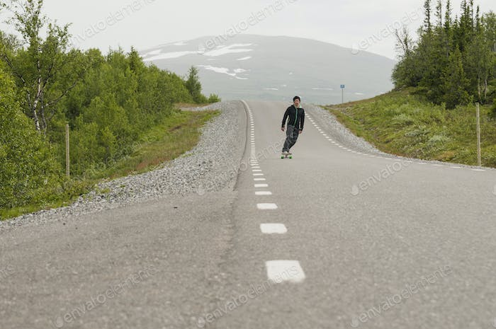 Man skateboarding on road