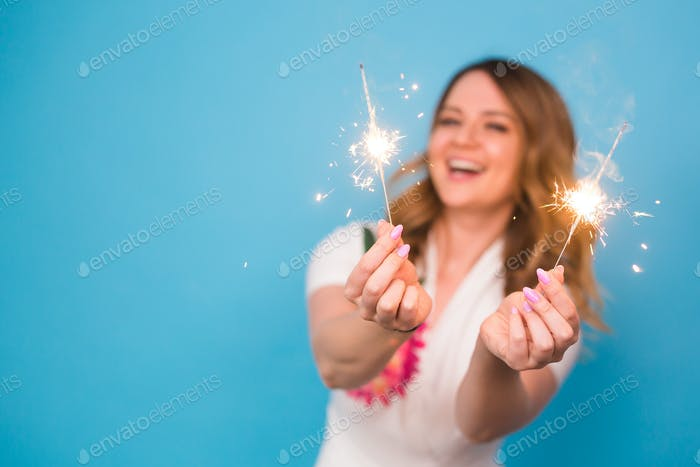 Woman holding bengal lights over blue background with copy space