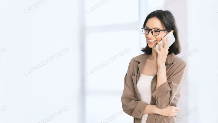 European girl talking on cell phone at office looking away