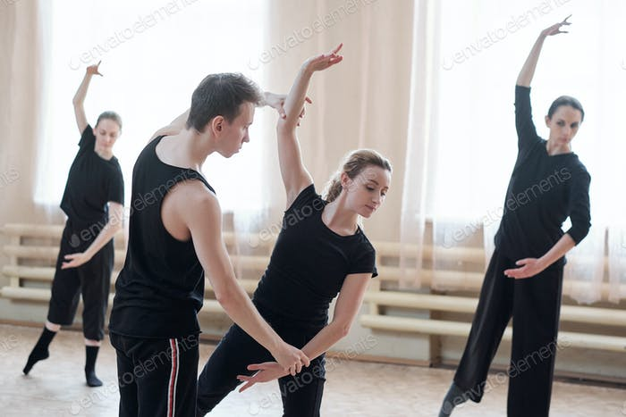 Fit male instructor of dancing course standing by one of girls in activewear