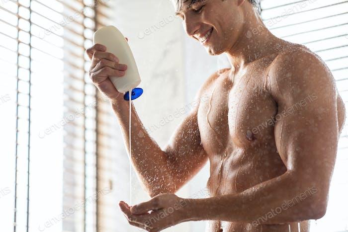 Schöner junger Mann gießt Shampoo auf die Hände