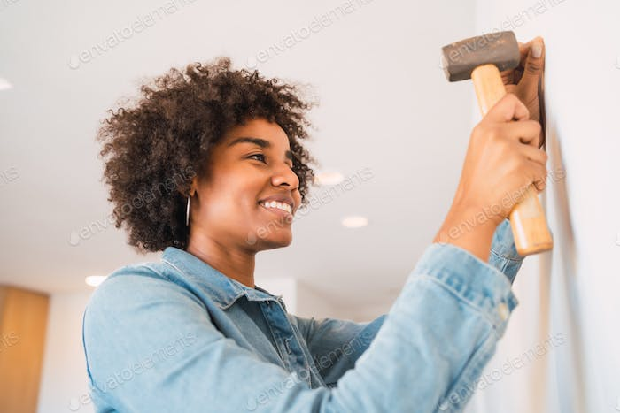 Afro woman hammering nail on the wall at home.