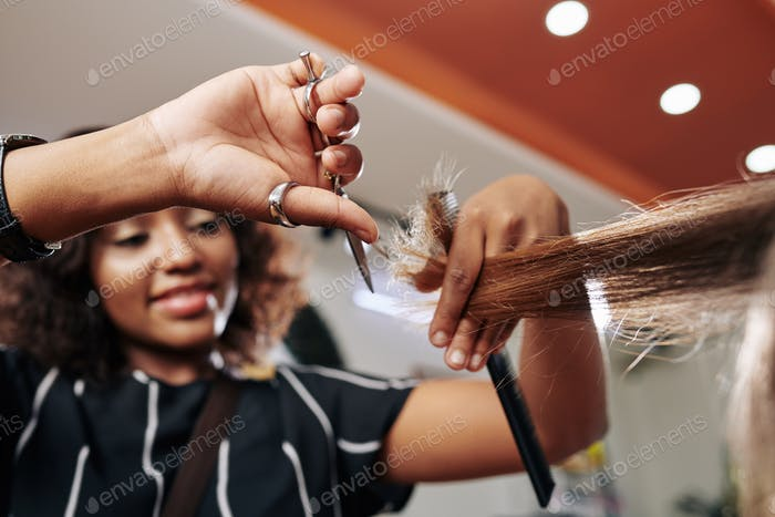 Smiling hairdresser cutting split ends