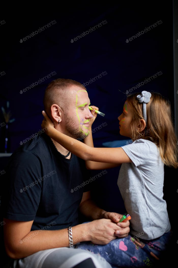 Daughter and father paint a face, having fun, leisure together at home