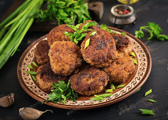 Juicy delicious meat cutlets on a dark table. Russian cuisine.