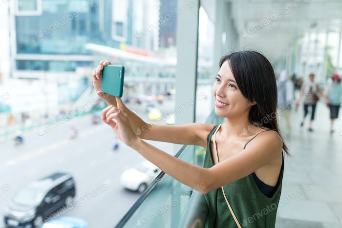 Woman taking photo with mobile phone in Bangkok city