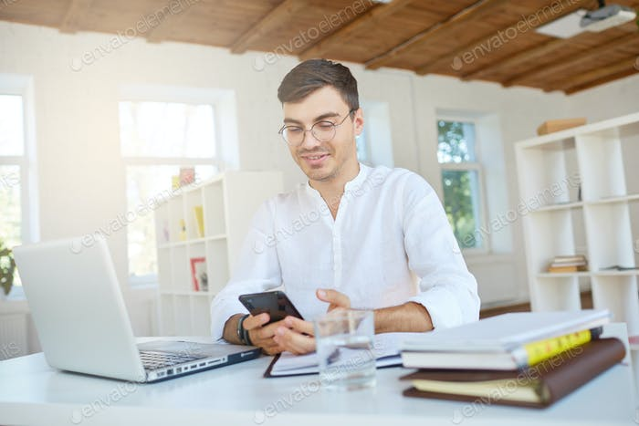 young businessman wears white shirt and glasses with laptop and mobile phone feels happy